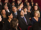 Man raising hand in theater audience - CAIF08122