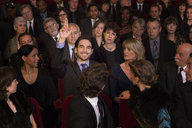 Man raising hand in theater audience - CAIF08128