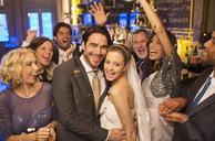 Friends cheering around smiling bride and groom at wedding reception - CAIF08149
