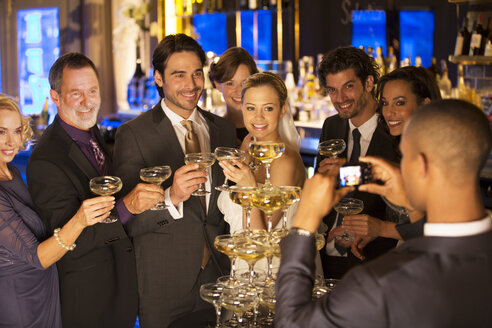 Man photographing bride and groom with friends at champagne pyramid - CAIF08152