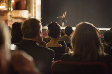 Rear view of theater audience watching performers on stage - CAIF08161