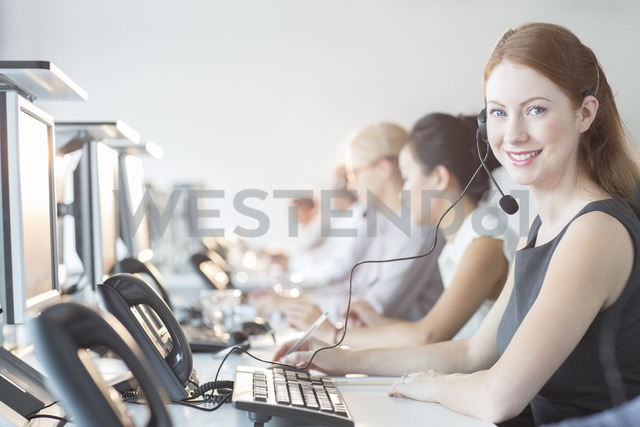 Businesswoman wearing headset in office - CAIF08170