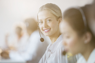 Businesswoman wearing headset in office - CAIF08173