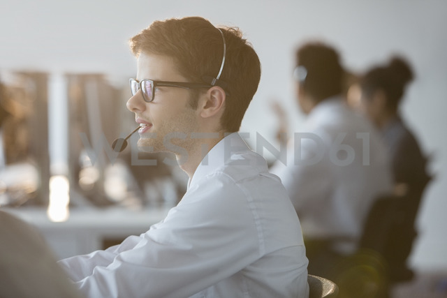 Businessman wearing headset in office - CAIF08176 - Tom Merton/Westend61