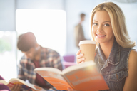 University student reading and drinking coffee - CAIF08182