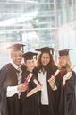 Smiling graduates holding diplomas - CAIF08197