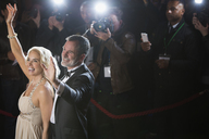 Celebrity couple waving to paparazzi at red carpet event - CAIF08242
