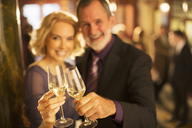 Portrait of well dressed couple toasting champagne glasses in theater lobby - CAIF08275