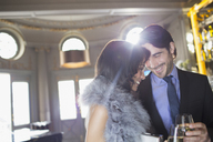 Well dressed couple drinking champagne in luxury bar - CAIF08308