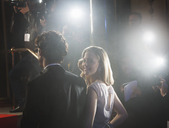 Paparazzi photographing celebrity couple at red carpet event - CAIF08314