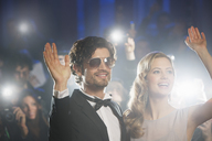 Well dressed celebrity couple waving to paparazzi - CAIF08317