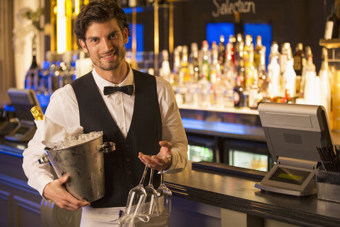 Portrait of well dressed bartender holding champagne bucket in luxury bar - CAIF08329