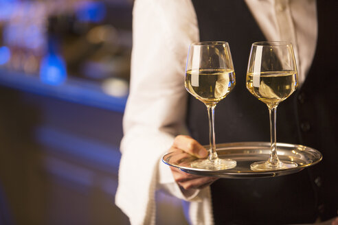 Close up bartender carrying white wine glasses on tray - CAIF08332