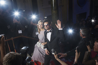 Well dressed celebrity couple waving to paparazzi on red carpet - CAIF08341