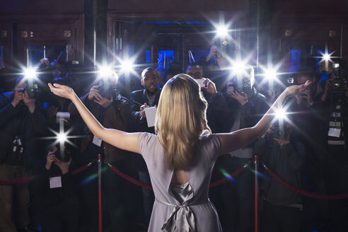 Rear view of female celebrity with arms outstretched to paparazzi at red carpet event - CAIF08344