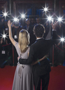 Rear view of well dressed celebrity couple waving to paparazzi on red carpet - CAIF08347