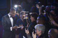 Well dressed male celebrity signing autographs at red carpet event - CAIF08353