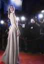 Well dressed female celebrity posing for paparazzi on red carpet - CAIF08359