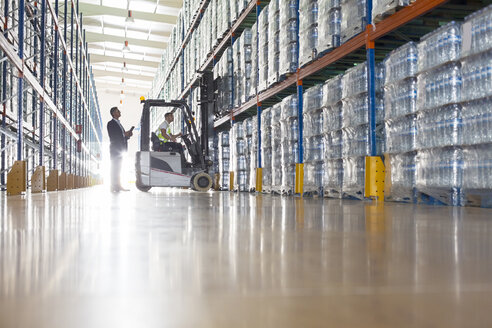 Workers with forklift in bottling warehouse - CAIF08404