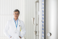 Scientist smiling in food processing plant - CAIF08422