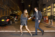 Cheerful couple holding hands and walking on city street at night - CAVF03482
