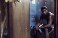 Boxer looking away while sitting in locker room - CAVF03530