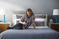 Woman using smart phone while sitting on bed at home - CAVF03569