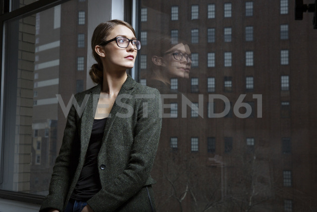 Businesswoman looking away while standing by window in office - CAVF03629
