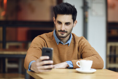 Portrait of young man sitting in a coffee shop using cell phone - JSMF00103