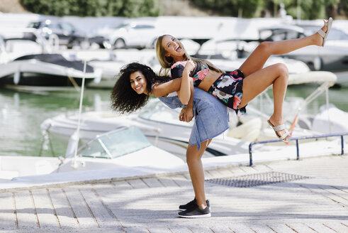 Two playful young women at waterfront promenade in summer - JSMF00111