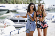 Two laughing young women at waterfront promenade in summer - JSMF00114