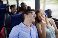 Happy couples sitting in bus - CAVF03723