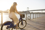 Happy woman riding bicycle on promenade during sunset - CAVF03759