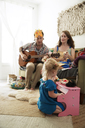 Daughter playing piano while parents sitting on sofa at home - CAVF03879