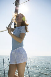Woman holding rope while standing in yacht - CAVF03906