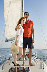 Full length of couple with arms around standing on yacht deck - CAVF03939