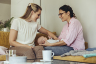 Midwife and mother giving newborn baby a belly massage to help with digestion - MFF04395