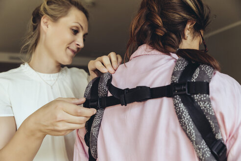 Midwife showing young mother how to fasten a baby sling - MFF04410