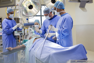 Team of doctors performing laparoscopic surgery in operating theater - CAIF08449