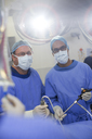 Two male surgeons wearing performing laparoscopic surgery in operating theater - CAIF08452