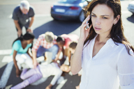 Woman calling emergency services at car accident - CAIF08521