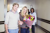 Couple carrying bouquet of flowers in hospital - CAIF08524