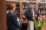 Businessman paying clerk at liquor store counter - CAIF08581