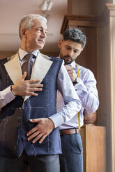 Tailor fitting businessman for suit in menswear shop - CAIF08614