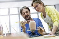 Mature couple painting pottery in studio - CAIF08659