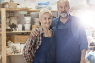 Portrait smiling senior couple wearing aprons in pottery studio - CAIF08680
