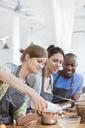 Friends enjoying cooking class in kitchen - CAIF08746