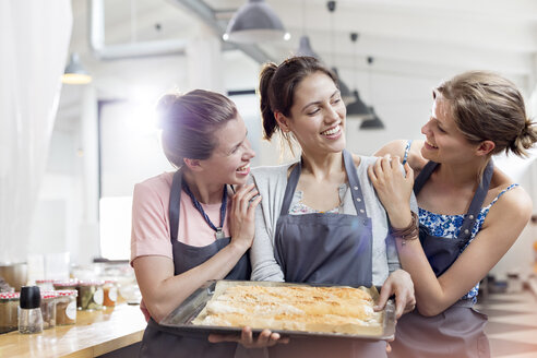 Smiling female friends enjoying cooking class in kitchen - CAIF08776