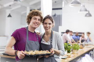 Portrait smiling couple with tray of food in cooking class kitchen - CAIF08779
