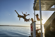 Young adult friends jumping from summer houseboat into sunny ocean - CAIF08785